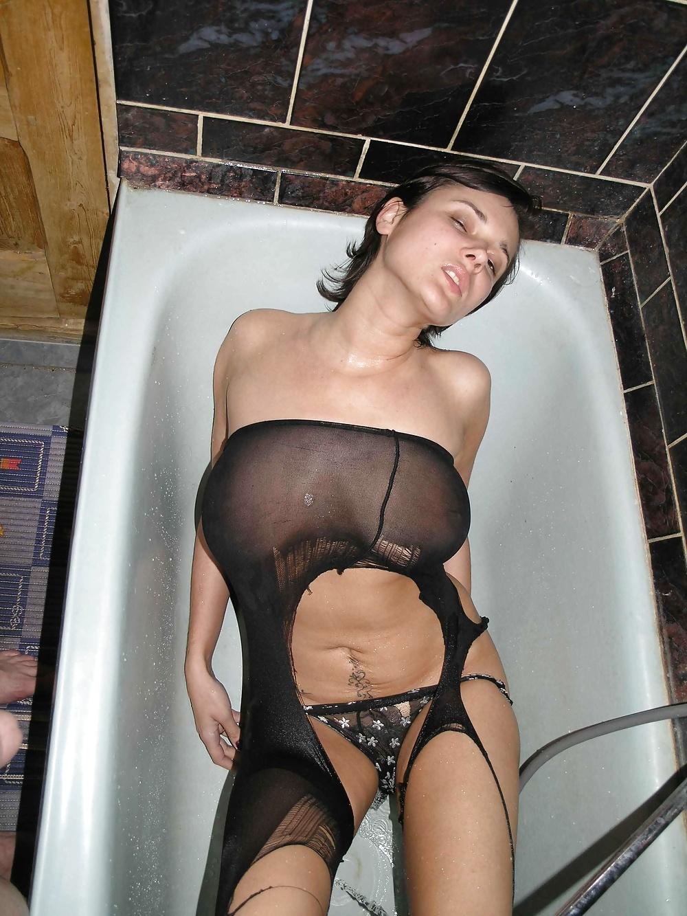 Сисястая брюнетка купается в ванне в порванных колготках