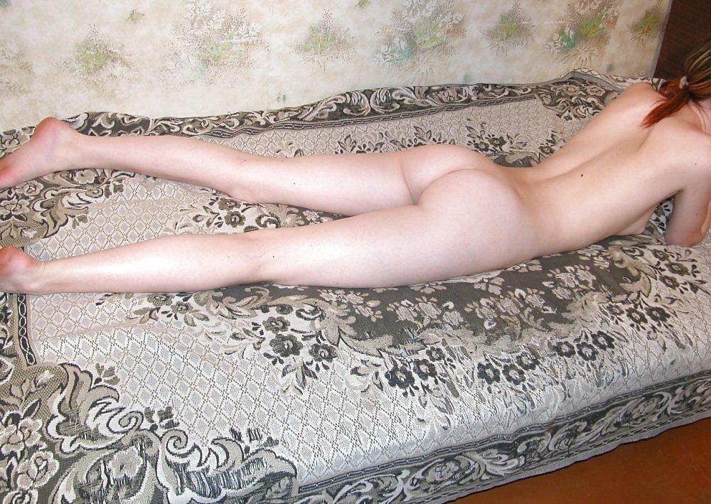 Молодая девка с гладкой киской у себя дома тренируется фотографироваться на камеру без лифчика