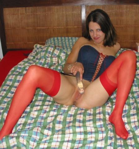 Темненькая девушка в красных чулочках на постели трахает себя искуственным членом