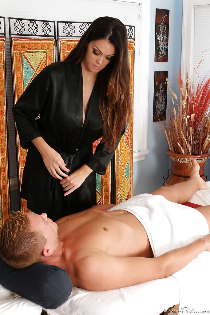Длинноволосая массажистка играет с членом клиента лежащего на кушетке