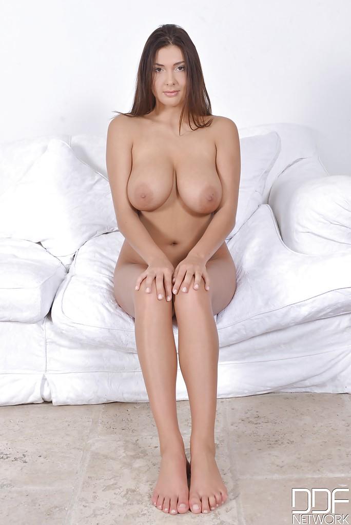 Девка с огромными дойками сидя на кушетке демонстрирует ступни