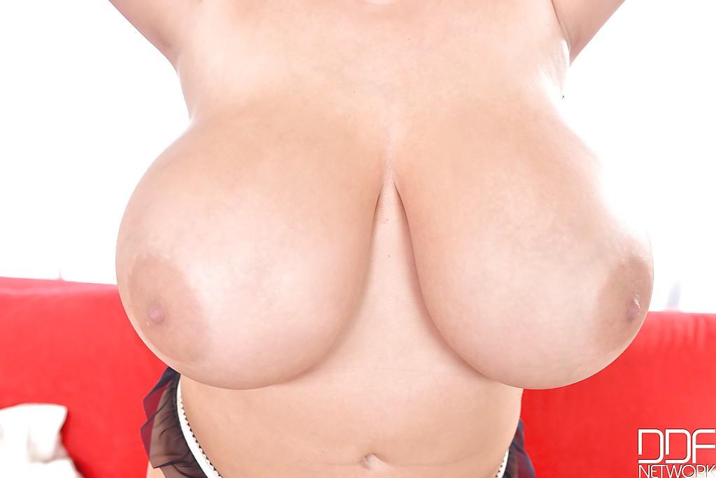 Толстушка в черных чулках показывает гигантские сиськи на красном диване