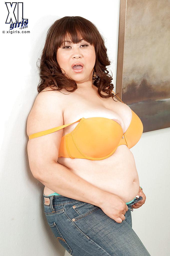 Толстая барышня снимает оранжевый лифчик в спальне