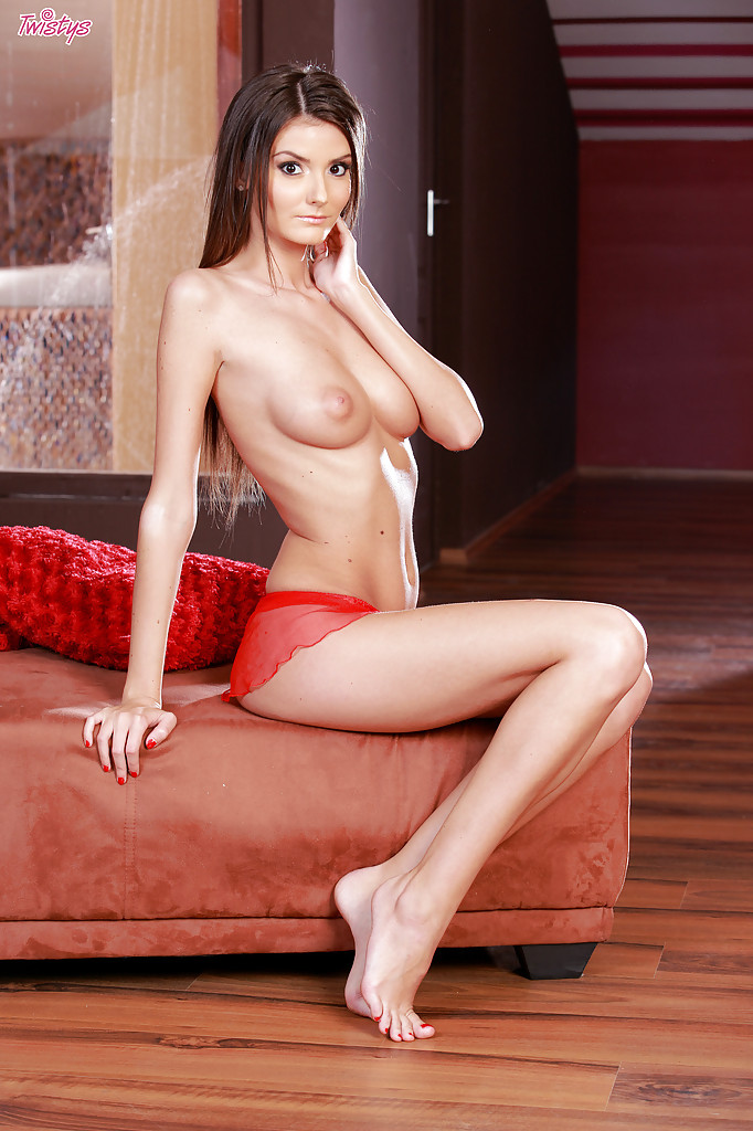 Длинноногая красавица в красном белье сексуально позирует перед камерой