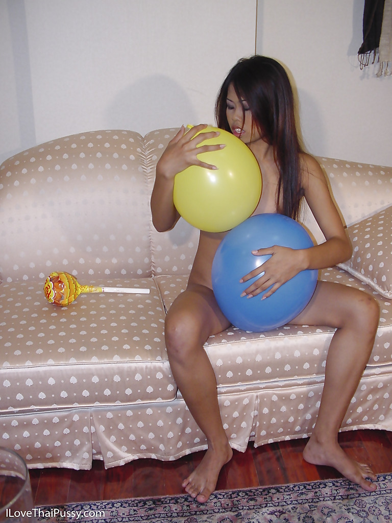 Подтянутая японка лежит на софе среди надувных шариков