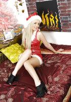 Блондинистая краля позирует на кровати в шапочке Санты 2 фотография