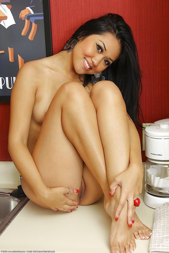Красивая азиатка шалит на кухне