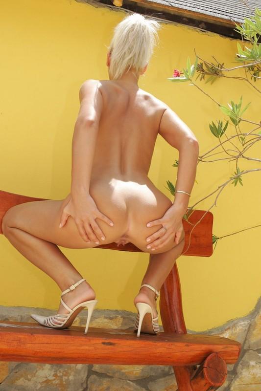 Смуглая светлая порноактриса сидит на скамейке за гаражом без одежды