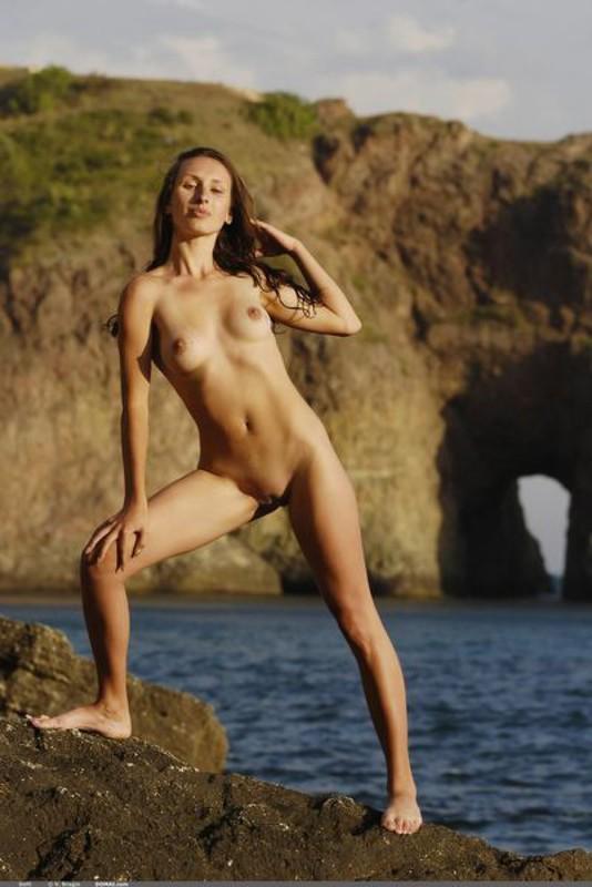 Девка с плоским животиком делает селфи в морском заливе