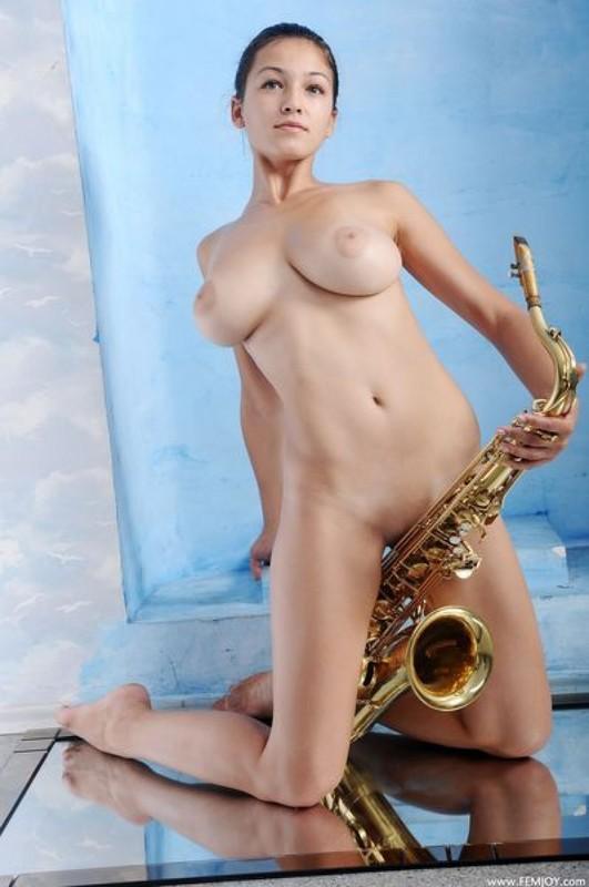 Раздетая музыкантка хвастается большими дойками рядом с саксофоном