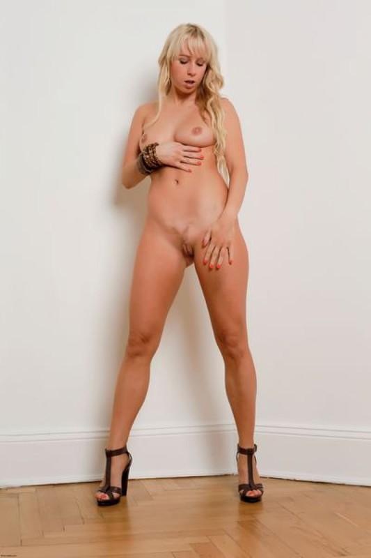 Длинноволосая блондинка трахает себя пальчиками возле белой стены
