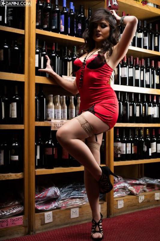 Длинноволосая леди с вызывающим макияжем позирует в винном магазине