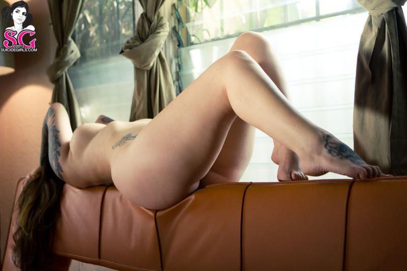 Татуированная чика красуется голым телом на коричневом диване