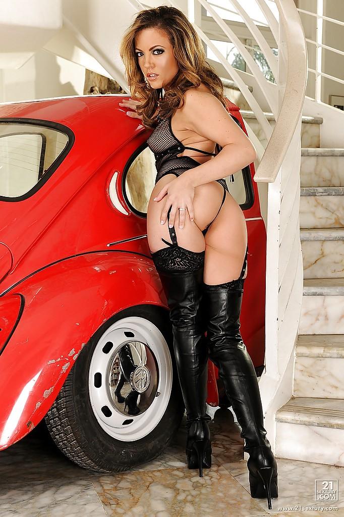 Бестия в ботфортах ласкает писечку возле красной машины