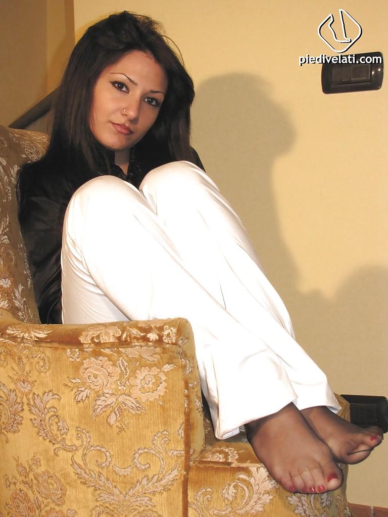 Кокетка показывает ступни в капроновых носочках сидя в кресле