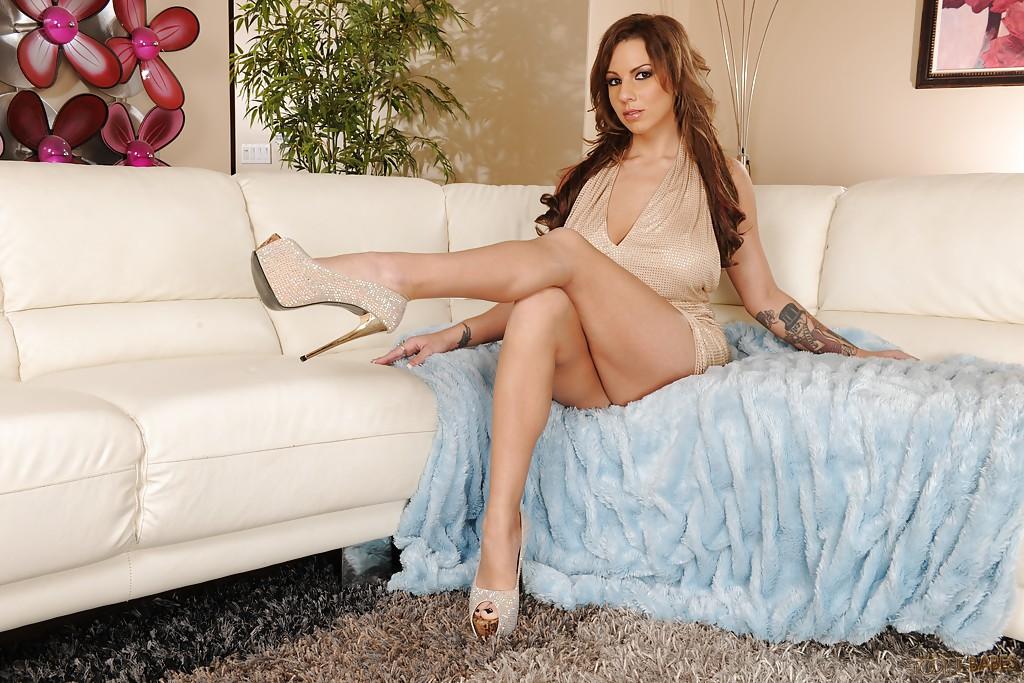Милашка не носящая трусики показывает голые ступни на диване
