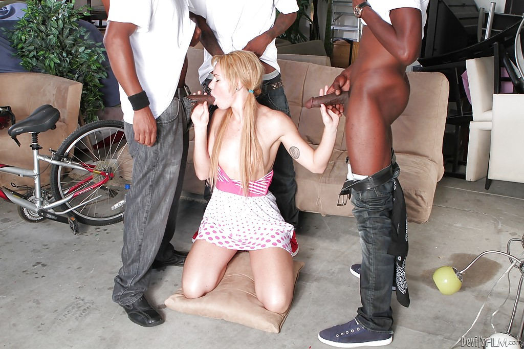 Давалка с красивыми волосами стоя на коленях отсасыват трем неграм