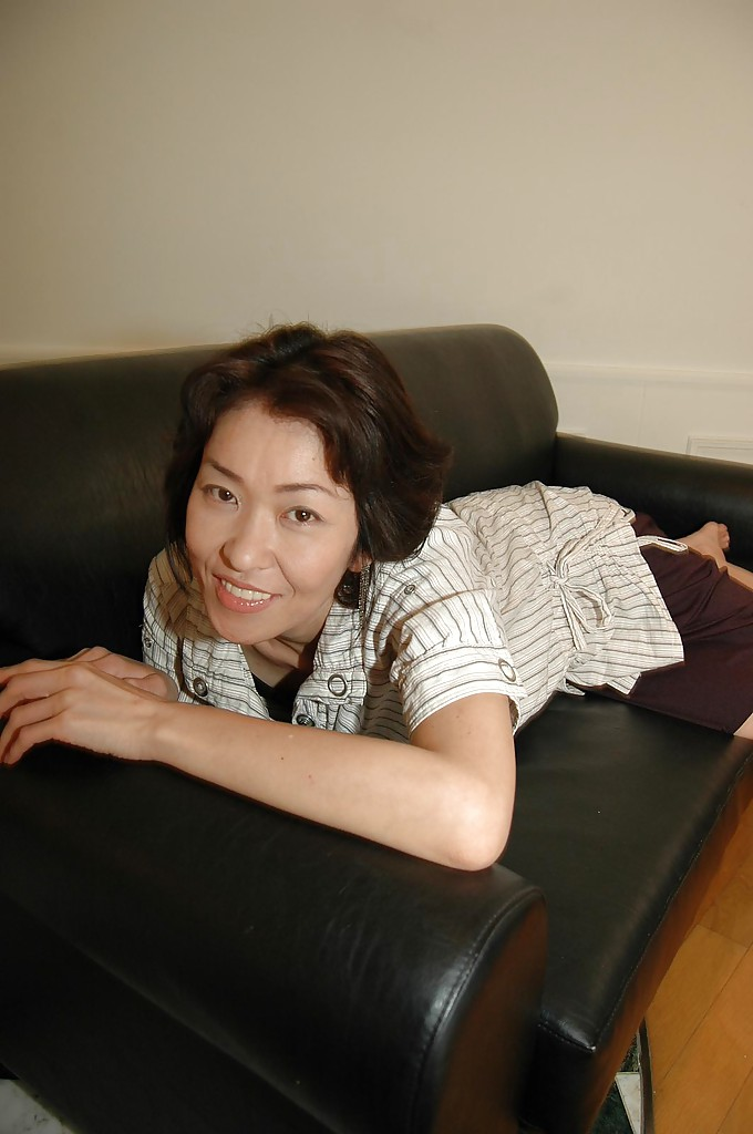 Возрастная китаянка в рубашке на кушетке теребонькает пизду фаллоимитатором