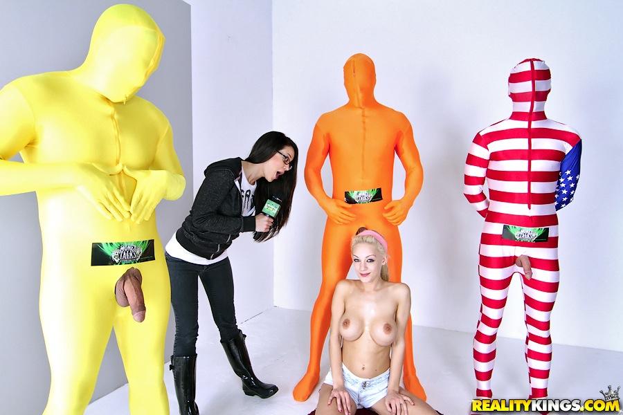 Ведущая смотрит как участница телешоу ублажает трех мужиков в цветных костюмах секс фото