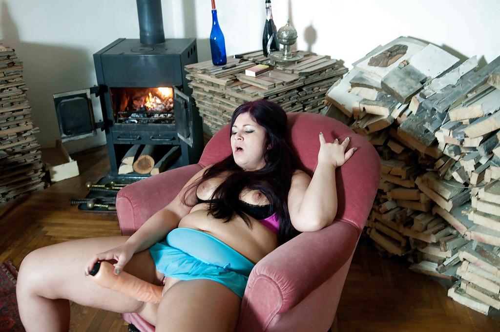 Сидя в кресле толстая баба трахает вагину фаллоимитатором