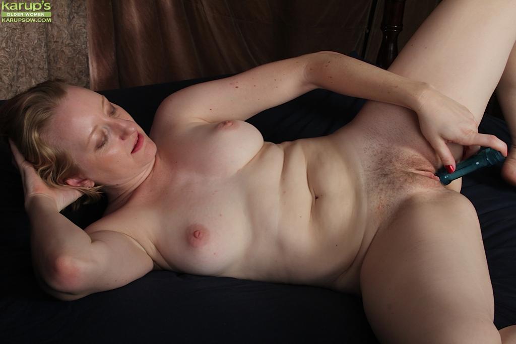 Зрелая тёлка на кровати трахает искуственным членом киску со щетиной