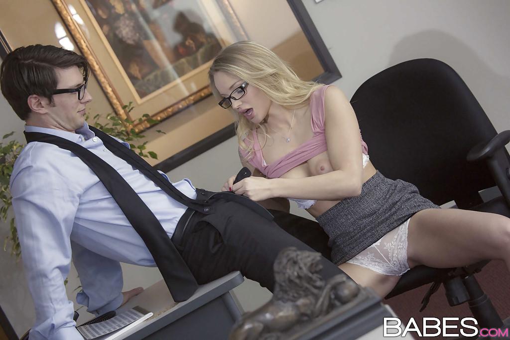 Молодая секретарша в очках шалит с коллегой на рабочем месте