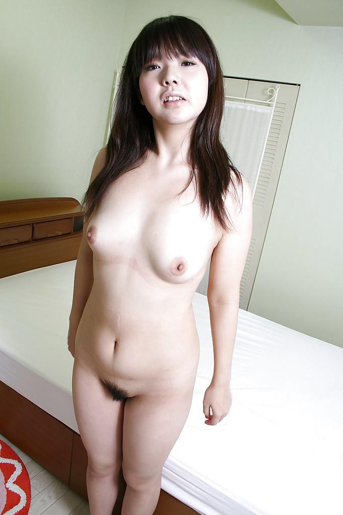 Азиатка с круглым личиком сидя на койке обнажает грудь и мохнатую киску