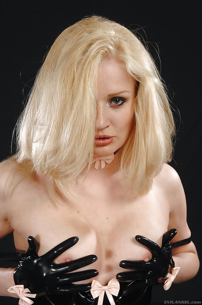 Модель со свелыми волосами в латексном боди и в светлых чулочках фотографируется в студии