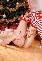Кареглазая брюнетка мастурбирует новогодней игрушкой возле наряженной елки 6 фотография