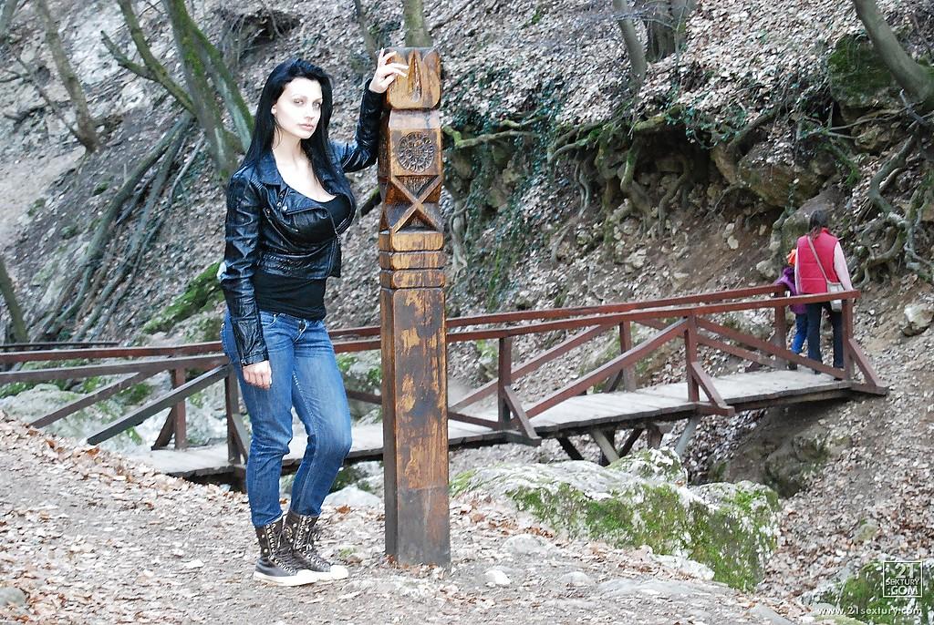 Синеглазая модель с темными волосами с пирсингом в языке сосет в лесу