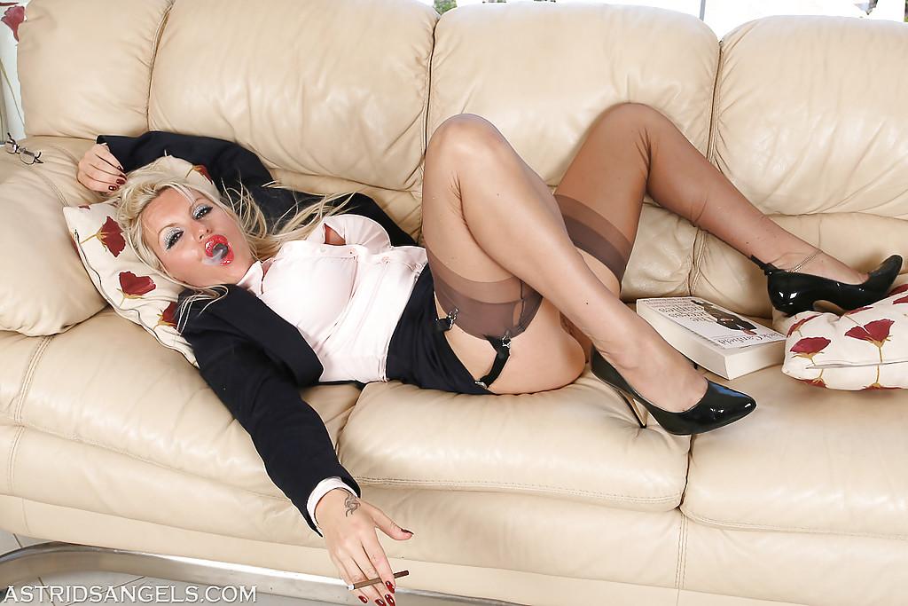 Матерая фотомодель в гольфах курит лежа на диване в вызывающих позах