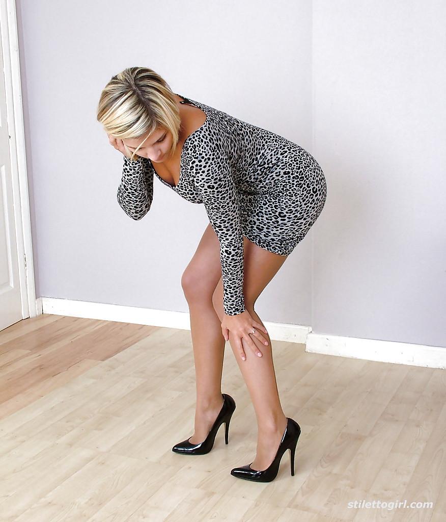 Блондинка в пятнистом платье хвастается ноги облаченные в бежевый капрон