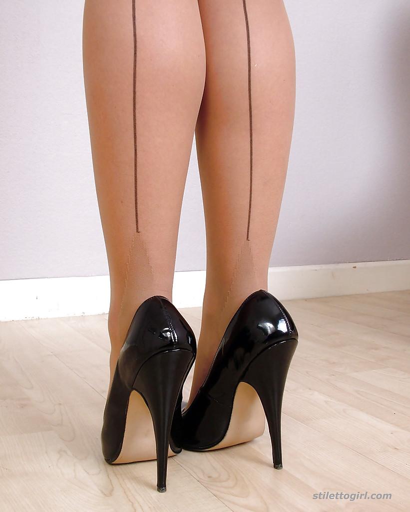 Блонда в пятнистом платье демонстрирует ножки облаченные в бежевый капрон