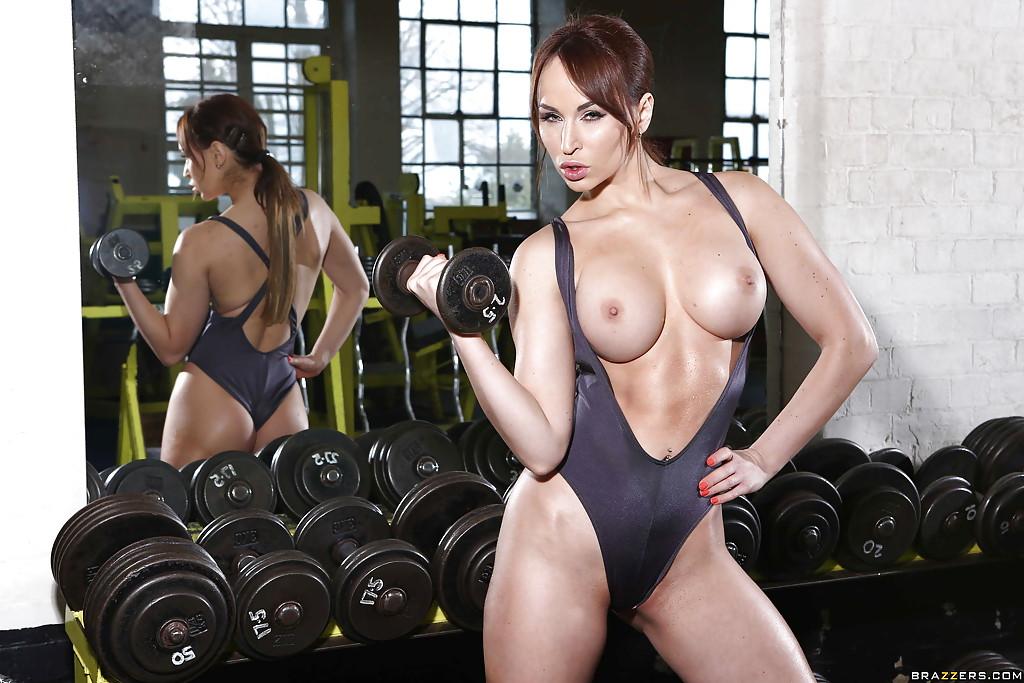 Спортсменка бахвалится искуственными буферами во время тренировки