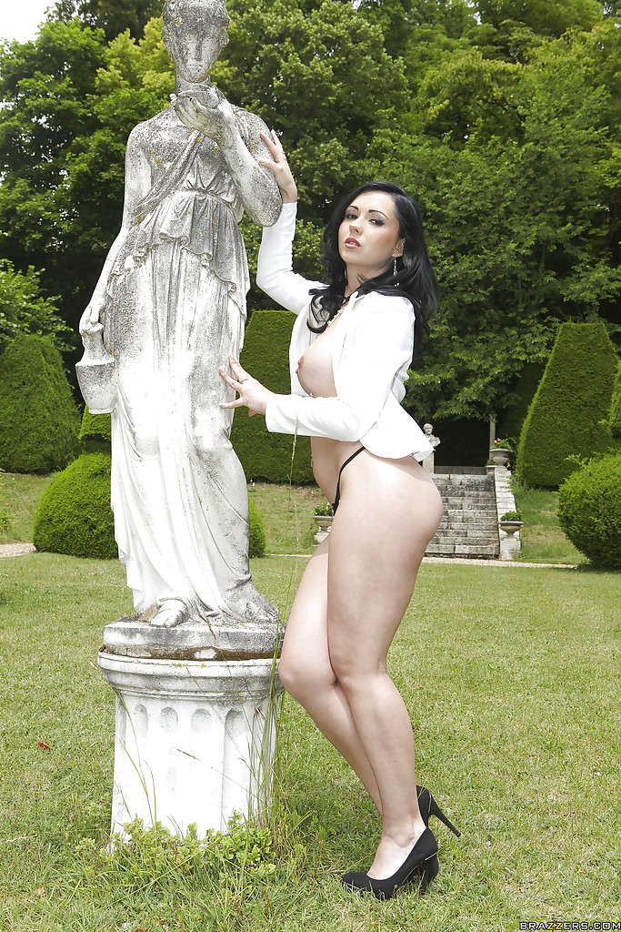 Брюнетка с округлой грудью раздевается на лице рядом со статуей