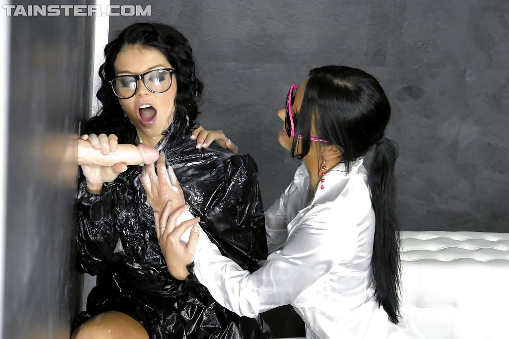 Торчащий из стены фаллоимитатор поливает спермой лесбияночек в очках