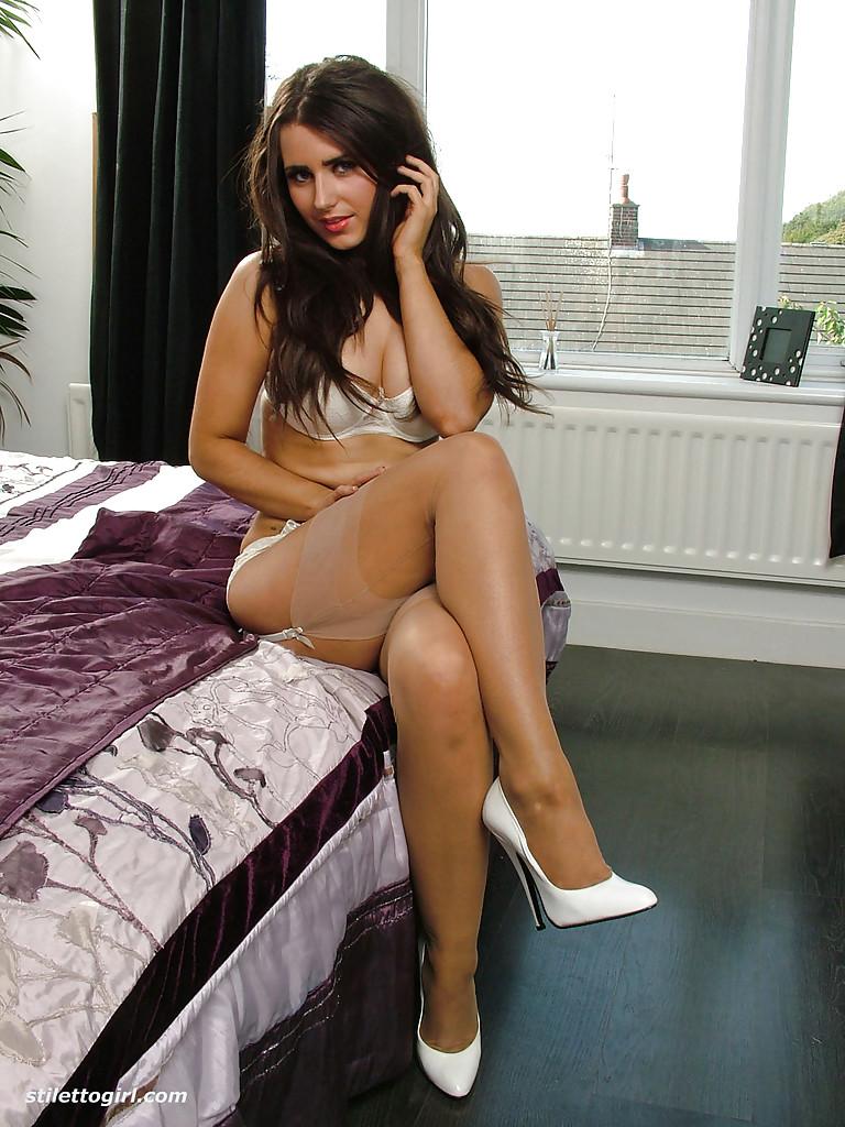 Длинноволосая сучка сидит на краю кровати в интимном белье