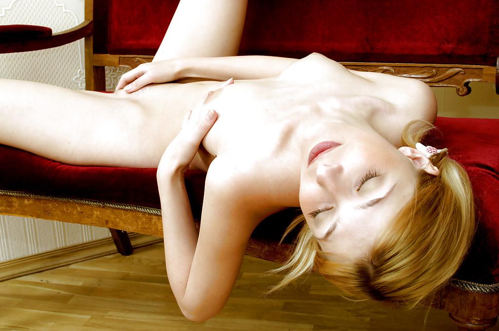Красотка с прекрасными ножками снимает с себя клетчатое платье на софе