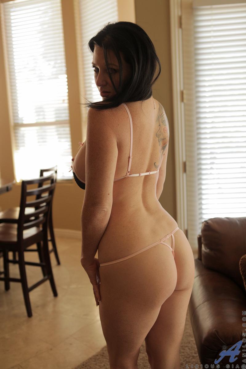 Брюнетистая милфа красуется в гостиной в возбуждающем нижнем белье