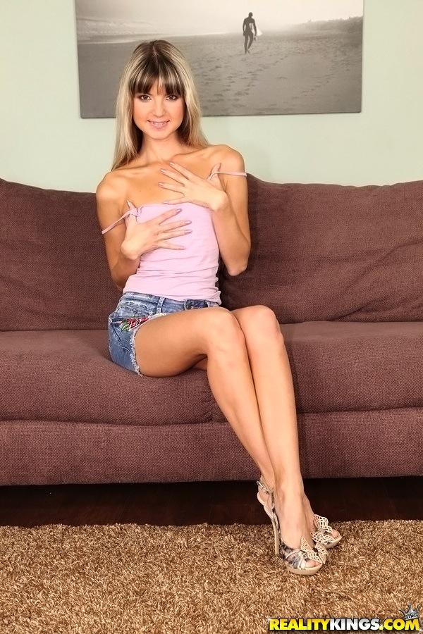 Сидя на диване длинноногая чика с милированными волосами светит дырочками
