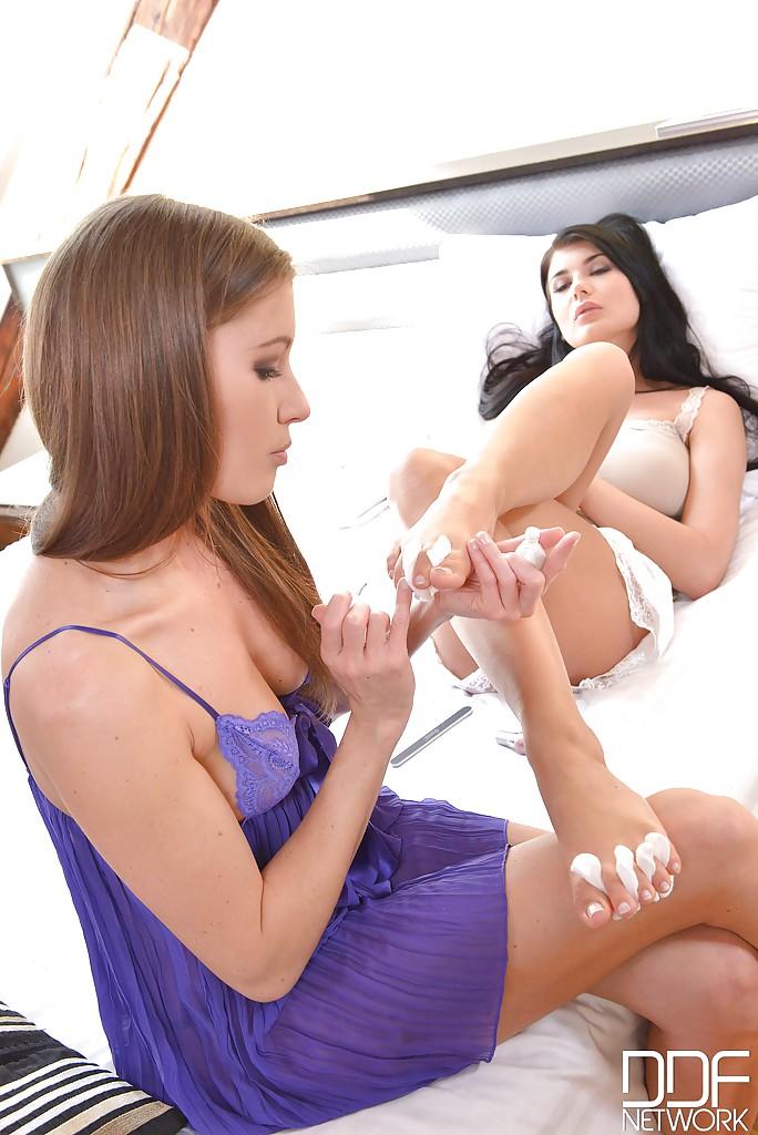 В спальне брюнетка балуется с раздетой лесбияночкой ухоженными ногами