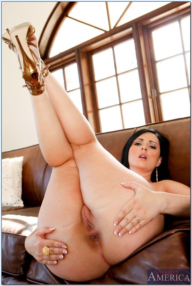 Брюнеточка с упругой попкой сексуально позирует на кожаном диване