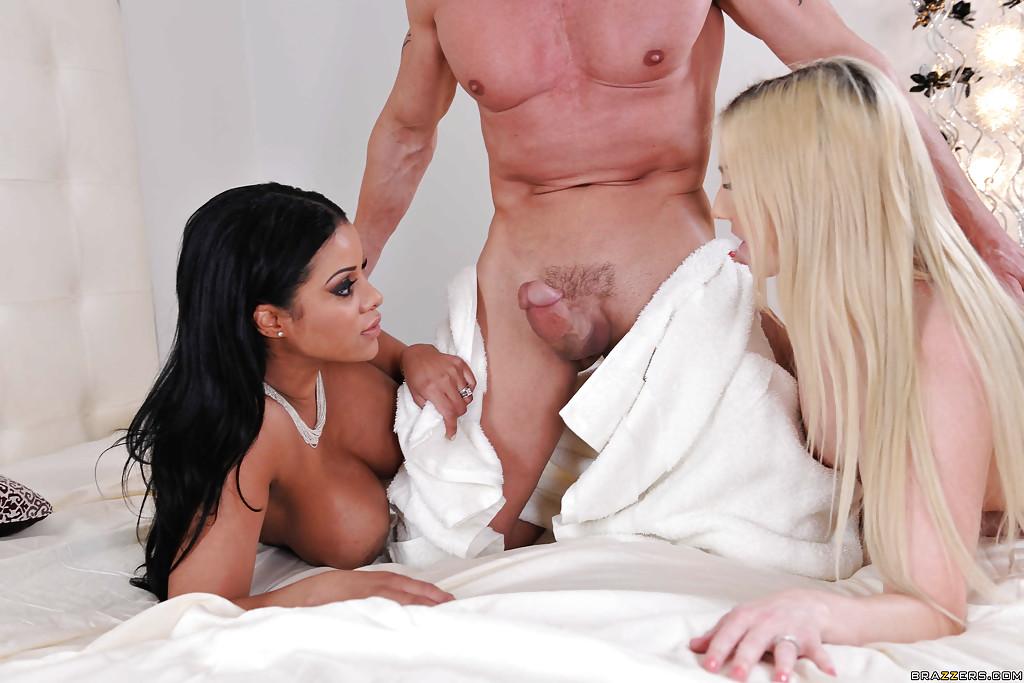 Блондинка вместе со смуглой шатенкой удовлетворяют член кавалера на кроватке секс фото