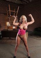 Сидя на деревянном стуле блонда в синей юбке показывает грудь и киску 15 фото