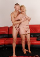 Блондинистая бабушка совокупляется с молодым парнем на красном диване 1 фотография