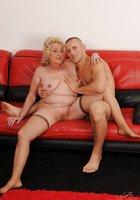 Блондинистая бабушка совокупляется с молодым парнем на красном диване 2 фотография