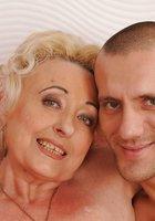 Блондинистая бабушка совокупляется с молодым парнем на красном диване 3 фотография