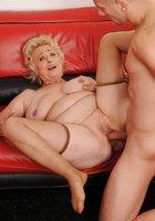 Блондинистая бабушка совокупляется с молодым парнем на красном диване 7 фотография