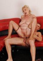 Блондинистая бабушка совокупляется с молодым парнем на красном диване 9 фотография