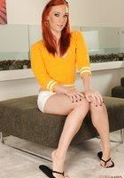 Рыжая красотка хвастается ножками с педикюром на пуфе 1 фотография